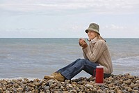 Woman having drink by the sea