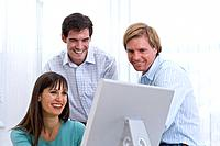 Businessman and colleague looking at woman's monitor, smiling