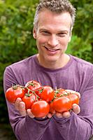 Man with handful of tomatoes, portrait