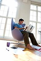 Man with laptop computer in armchair, low angle view