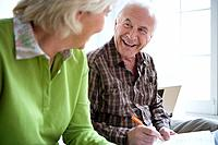 Senior couple smiling at each other, man signing paperwork