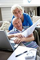 Senior couple with laptop computer and paperwork, smiling, portrait