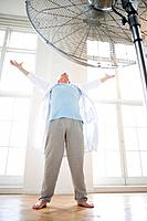 Senior man with arms raised by fan, low angle view