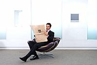 Businessman reading newspaper in armchair