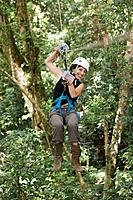 Hispanic woman swinging on zip line,