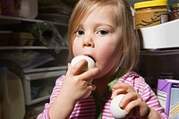 Girl trying to eat egg