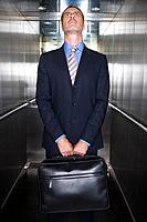Businessman in elevator, looking up