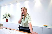 Receptionist behind desk on telephone