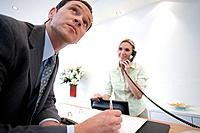 Businessman signing at reception by receptionist on telephone