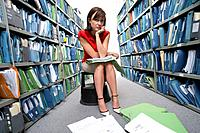 Businesswoman on stool by shelves of files, portrait