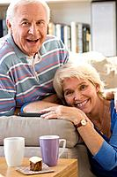 Senior couple in living room, smiling, portrait