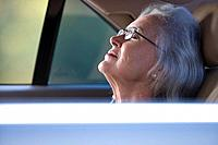 Senior woman with eyes closed in back seat of car