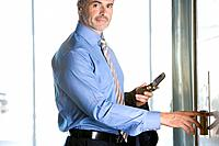 Businessman with cell phone using elevator