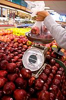 Woman weighing apples in grocery store