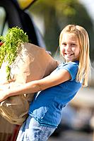 Girl loading groceries into car