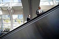 Businessmen using escalators in airport