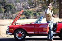 Man talking on cell phone next to broken down red convertible