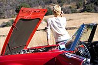 Woman talking on cell phone next to broken down red convertible