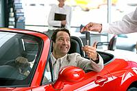 Salesman handing man keys to new red convertible