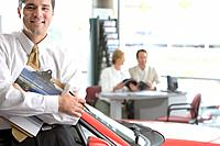 Salesman posing in car showroom