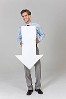 Businessman holding arrow sign, portrait