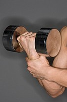Muscular man holding dumbbell, close_up