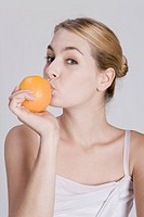Young woman kissing orange, portrait