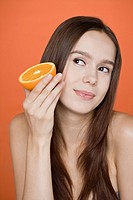 Young Woman holding orange slice, portrait