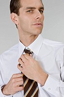 Businessperson tying tie, close_up