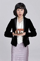 Businesswoman holding miniature house on palm, portrait