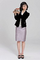 Businesswoman holding miniature house and paper currency on palm