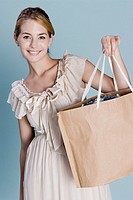 Young woman holding shopping bag, portrait