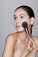 Young woman applying make_up brush, close_up