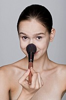 Young woman holding make_up brush, portrait