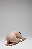Naked young woman crouching, rear view