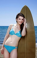 Female young adult posing with surfboard