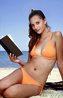Female young adult reading book on beach