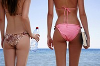 Backside of two female young adults on the beach