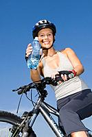 Young woman with mountainbike and water bottle