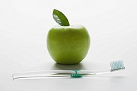 Close_up of toothbrush with apple