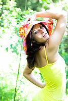 cute dark-haired woman in yellow shirt with a colourful hat, posing in a forest