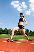 young woman wearing running clothes, stretching on a running track