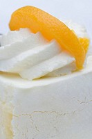 Close_up of cream cake with orange slice