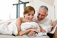 mature couple reading magazine in bed