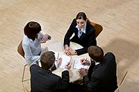 high angle view of four business people sitting around conference table