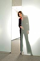 businesswoman peeking behind half open glass door