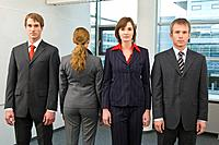 portrait of four business people standing in line one standing with back to camera
