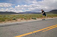 A man skateboarding down a desert road near Pyramid Lake NV