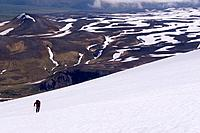 A skier climbing Mount Vsevidov in the Aleutian islands Alaska with the tundra below