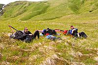 Three hikers taking a break on Umnak Island in the Aleutian Islands Alaska